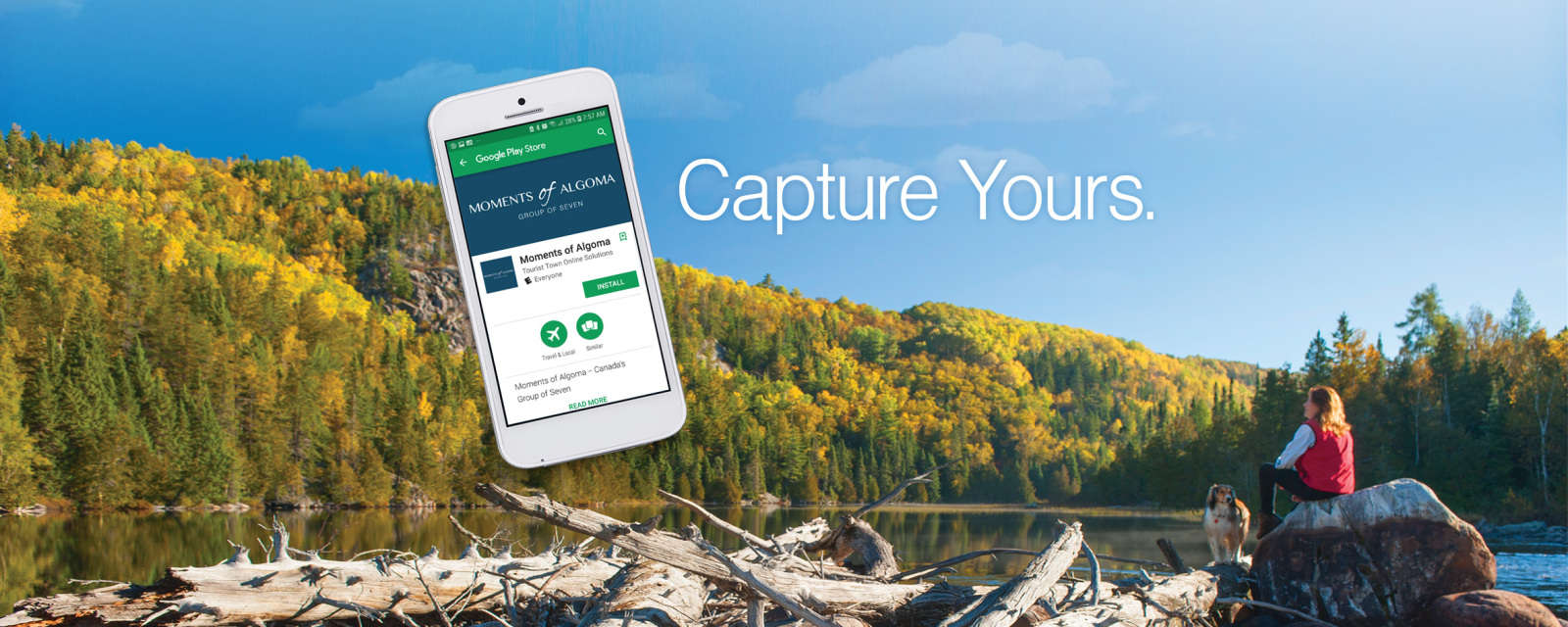 An image of a mobile phone over top of a scenic image of a woman and dog sitting on a rock overlooking a lake with fall foilage.